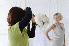 A female photographer takes a beautiful model in the studio stock image