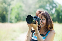 Female photographer takes photo Royalty Free Stock Photo