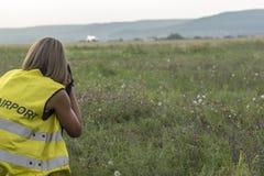A female photographer takes photos of take-off plane stock photo