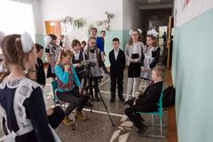 Female photographer takes pictures of smart first-graders after the lessons in the school corridor. Belogorsk, Kemerovo region / RF - March 22, 2018: A female stock photography