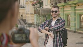 Female photographer taking a photo of the man in the street of an old city with beautiful architecture. Tourist takes. Picture of her friend. The funny guy stock video