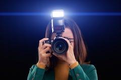 Using camera flash. Female photographer taking photos with flash, isolated on dark royalty free stock image