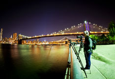 Female photographer. Taking a picture in front of Brooklyn Bridge Royalty Free Stock Images