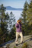 Female photographer taking picture. Young female photographer standing on the top of the mountain on big rock and taking picture. Front view. Trees and mountain Royalty Free Stock Image