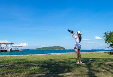 Female photographer taking pictures of the beautiful beach. And blue sky Royalty Free Stock Photo