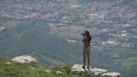 Female photographer taking pictures of landscape stock video footage