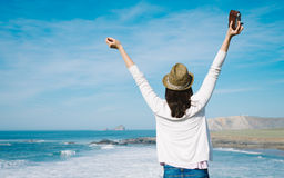 Female photographer travel and freedom. Hipster woman enjoy freedom on vacation travel. Successful funky girl raising arms towards the sea in Asturias coast Royalty Free Stock Photo