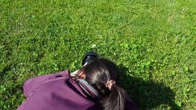 Female photographer using DSLR camera on grass. Shooting dandelion stock video footage
