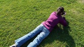 Female photographer using DSLR camera on grass. Shooting dandelion stock video
