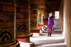 Walking by prayer wheel. A female photographer walking by the prayer wheel in the Tibetan Magnificent temples. Kangding in sichuan province of China Stock Photos
