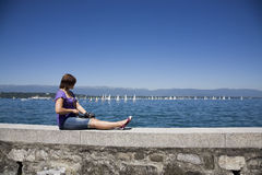 Female photographer by the water. Young woman relaxing by the water watching sailig boats Stock Images