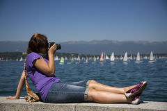 Female photographer by the water. Young woman relaxing and taking pictures by the water Stock Photo