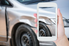 Female photographing her vehicle with damages. For accident insurance Royalty Free Stock Photo