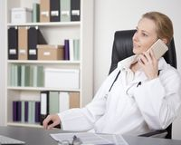 Female Physician on Chair Calling on Mobile Phone Stock Image
