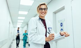 Female physician in hospital corridor writing prescription. Portrait of happy young female physician standing in corridor with clipboard. Caucasian women working Stock Photos