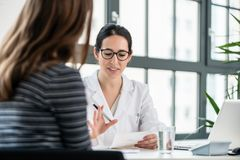 Female physician listening to her patient during consultation in. Female physician listening to her patient during consultation while sitting down in the office stock photo