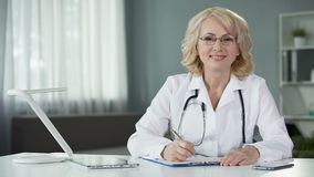 Female physician making prescriptions filling out patients medical records