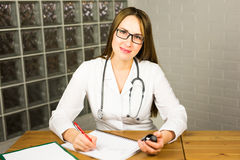 Female physician medicine doctor or pharmacist sitting at work table, holding jar or bottle of pills in hand and writing Stock Photo