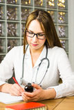 Female physician medicine doctor or pharmacist sitting at work table, holding jar or bottle of pills in hand and writing Royalty Free Stock Images