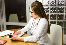 Female physician medicine doctor or pharmacist sitting at work table, holding jar or bottle of pills in hand and writing Stock Photography