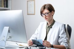 Female physician at modern medical doctor office. Woman practitioner examining x-ray at workplace in front of a desktop computer royalty free stock images