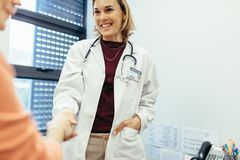 Female physician shaking hands with her patient. And smiling in clinic. Medical professional meeting women in hospital Stock Photos