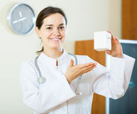 Female physician with stethoscope holding vitamin tablets in pac Stock Image