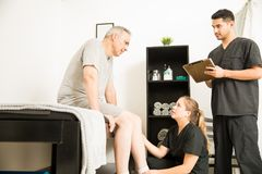 Physiotherapy Physician Talking To Customer While Colleague Taking Notes. Female physician talking to sad male customer while colleague taking notes in stock image