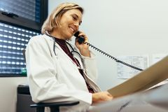 Female physician working at her office desk. Female doctor reading medical reports and  talking on phone at clinic. Physician working at her office desk Royalty Free Stock Photos