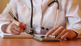 Female physician writes in notebook at the desc. Professional is using smartphone for searching info in the database. Female physician writes in notebook at the stock footage