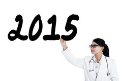 Female physician writes number 2015 on whiteboard Stock Images