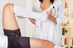Female physio therapist hands working on male patients lower leg and ankle, bending knee, blurry clinic background Stock Photography