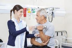 Female Physiotherapist Assisting Senior Man To Lift Dumbbell Stock Photos
