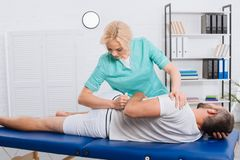 female physiotherapist doing massage to patient on massage table