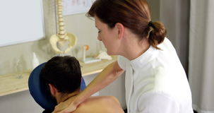 Female physiotherapist giving back massage to a patient