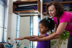 Female physiotherapist helping girl patient in performing exercise with dumbbell. In clinic Stock Photo