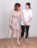Female Physiotherapist nurse. Helping a young women on crutches Stock Image