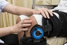 Physiotherapy adjusting walking brace on patient`s leg in. Female physiotherapy adjusting walking brace on patient`s leg in wheel chair Royalty Free Stock Photos