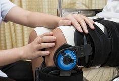 Physiotherapy adjusting walking brace on patient`s leg in. Female physiotherapy adjusting walking brace on patient`s leg in wheel chair royalty free stock photos
