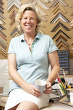 Female picture framer at work. Holding a mug and smiling at camera Stock Photography