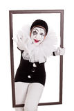 Female pierrot in a frame reaching hand to viewer Royalty Free Stock Image