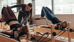 Female pilates trainer helping a pilates woman during training Royalty Free Stock Images