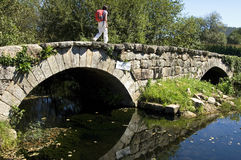 Female pilgrim walks on historic bridge, Portugal Royalty Free Stock Photos