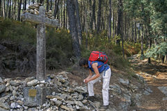 Female pilgrim on the Way of St. James in Portugal. On top of the mountain Portela Grande is the stone cross, cruz dos Franceses, also known, cruz dos Mortos or Stock Image