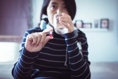 Female with pills or capsules on hand and a glass of water,Concept for health. Selective focus Royalty Free Stock Photo