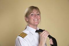 Female pilot adjusting her uniform tie Stock Photos