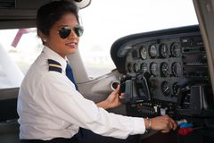 Female Pilot in the Cockpit. Close up of a young woman about to fly the aircraft. She is a pilot and is dressed in uniform Stock Photos