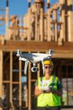 Female Pilot Flies Drone Quadcopter Inspecting Construction Site.  royalty free stock photo