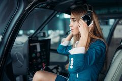 Female pilot in headphones in helicopter cabin Stock Photos