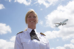 Female pilot with a passing passenger jet in sky Royalty Free Stock Photography